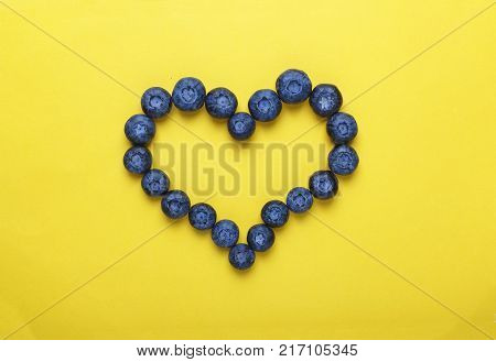 Style minimalism. Blueberries in the shape of heart on a yellow background. The concept: blueberries prevent heart disease