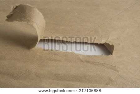 a tear in a piece of brown paper bag revealing white background
