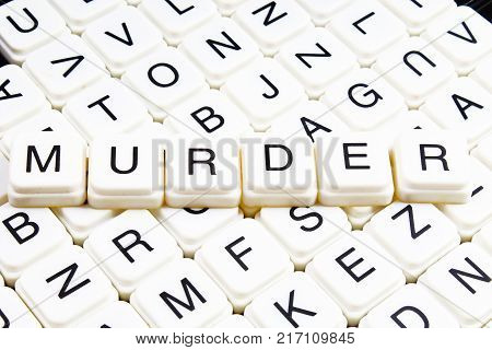 Murder text word crossword. Alphabet letter blocks game texture background. White alphabetical cubes blocks letters on crossword letters educational toy background. Murder title.