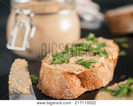 Extreme close up view of slice bread with homemade turkey pate and fresh green parsley on black kutting board over black cement background, Shallow DOF. Selective focus