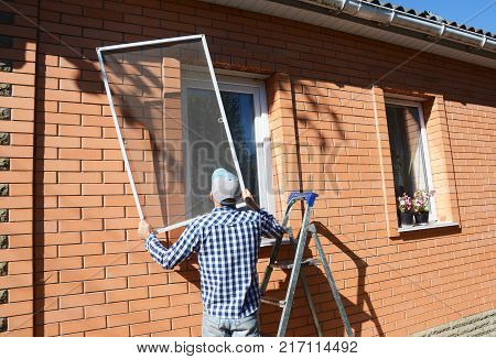 Worker install mosquito net or mosquito wire screen on brick house window.