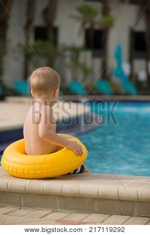 Back view on cute little toddler boy with lifeline sitting on the edge of the swimming pool ready to jump. Safety first.