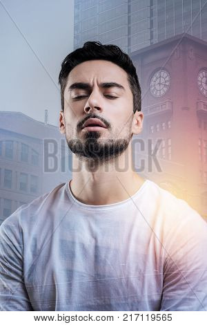 Eyes closed. Calm attentive young man looking concentrated while closing his eyes and trying to remember important information