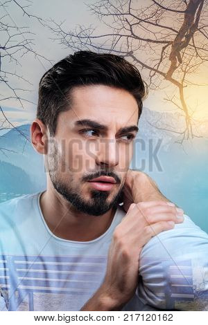 Strange feeling. Young bearded man frowning and touching his neck while having a strange sudden pain in it and feeling worried