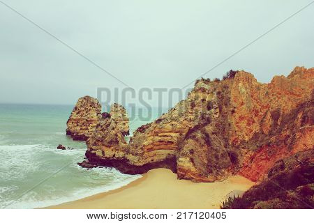 Camilo Beach in Lagos, Algarve Coast, Portugal Vintage Foggy Landscape Wallpaper. Panoramic Ocean View with Stone Cliff Rocks at Sandy Lagoon Beach Shore. Cloudy Sky and Gloomy Nature Background Scene