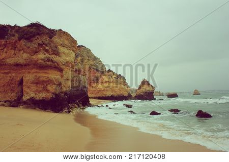 Foggy Landscape of Camilo Beach in Lagos, Algarve Coast, Portugal. Vintage Wallpaper, Panoramic Ocean View with Cliff Rocks and Waves at Sandy Beach Shore. Cloudy Sky and Gloomy Nature Background.