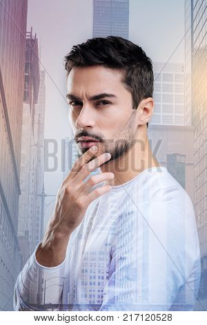Having suspicions. Qualified smart young accountant touching his lips and looking into the distance while thinking about the new strange unknown bank not far from him