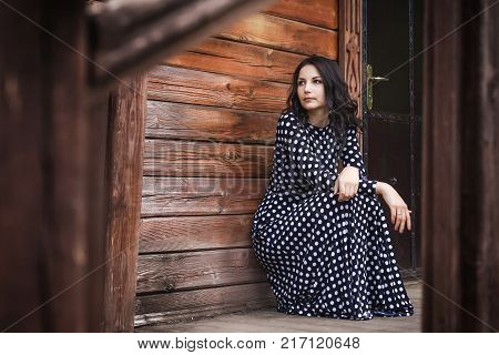 young pretty girl with long brunette hair in vintage black dress in white peas sitting near wooden house in the village