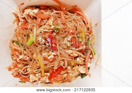 Pasta Wok with Vegetables and Meat in Paper To Go Box. Chinese and Thai Food Delivery Concept, Close Up of Asian Wok. Top View of Healthy Dietary Recipe of Pasta Meal, Isolated on White Background.