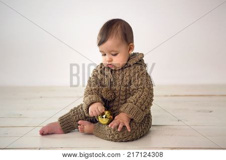 baby boy crawling on the floor in knitted brown dress