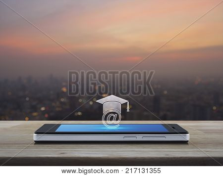 e-learning icon on modern smart phone screen on wooden table over blur of cityscape on warm light sundown Study online concept