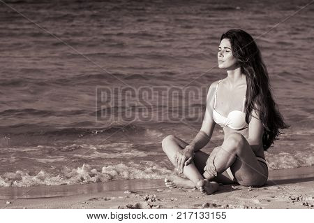 Black and white photo of a female sitting at the beach near sea waves and sunbathing. Young woman relaxing at the seaside. Model with ling curly hair wearing bikini