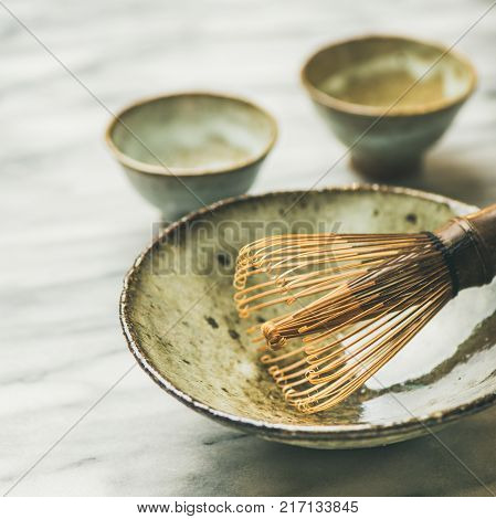 Japanese tools for brewing matcha tea. Matcha powder in tin can, Chasen bamboo whisk, Chawan bowl, cups for ceremony, grey marble background, selective focus
