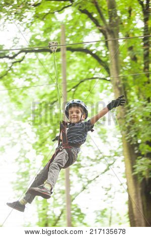 Boy in a helmet and safety equipment in adventure ropes park get down in the end of way