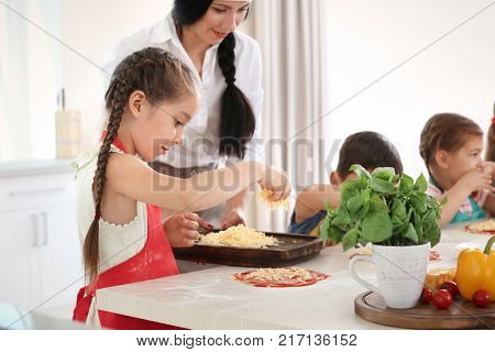 Children and teacher in kitchen during cooking classes