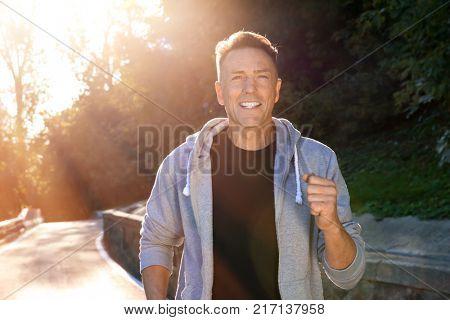 Mature sporty man running outdoors