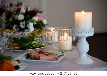 Festive table with food and candles. Christmas feast at the table with delicious dishes. New year feast.