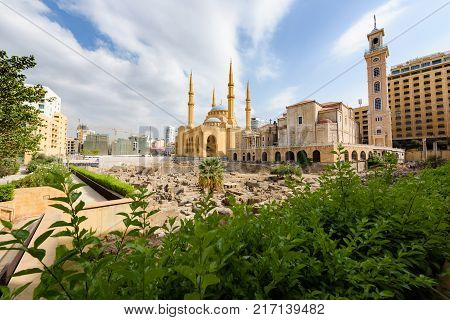 Saint George Maronite Cathedral and Mohammad Al Amine blue Mosque across roman ruins in downtown Beirut Lebanon.