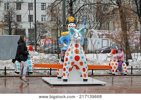 Moscow Russia - February 21 2017: Mother with daughter playing seesaw in Novopushkinsky square in Moscow. Traditional Dymkovo toy man on horse as art object and swing at Russian national festival