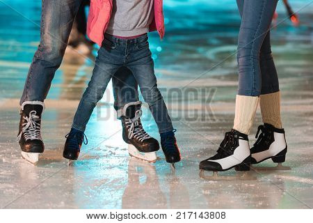 cropped shot of young family in skates skating together on rink