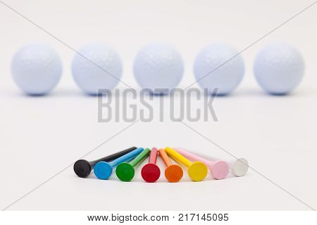 White golf balls and different wooden tees on the white table