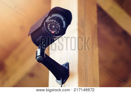 black security surveillance camera mounted on the wooden pole