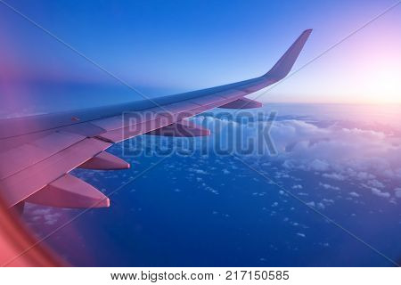 View from passenger's seat in airplane flying above clouds in dramatic sunset light. High resolution of image. Fast Travel and transportation concept