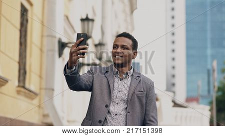 businessman having online video chat in business conference. Man using app on his smartphone to have conversation