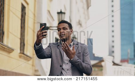 Upset  businessman having online video chat in business conference. Man using app on his smartphone to have conversation
