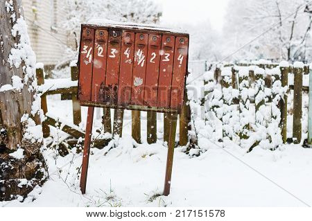 old rickety mailbox in the winter under the snow. Mailbox with written figures and peeling paint