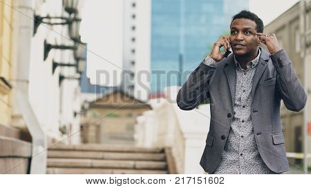 Upset Mixed race businessman having online video chat in business conference. Man using app on his smartphone to have conversation