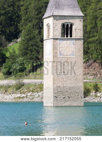 Submerged Tower Of Reschensee Church, Man Swimming Next To It