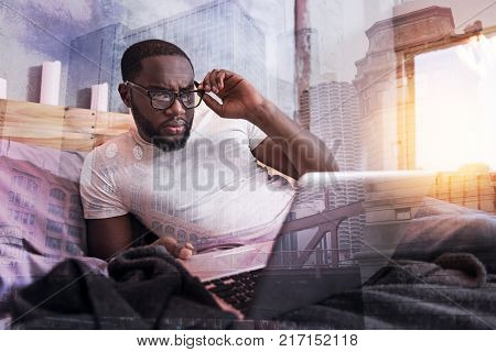 Remote work. Serious nice handsome man looking at the laptop screen and fixing his glasses while working remotely