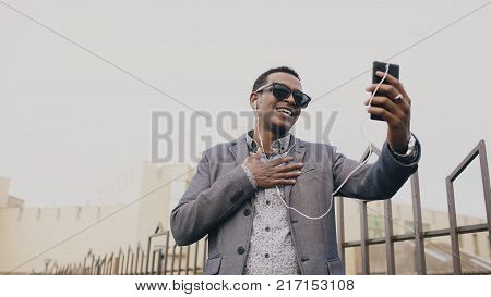 Mixed race businessman having online video chat in business conference. Man using app on his smartphone to have conversation