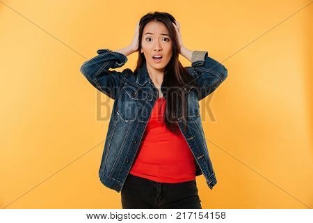 Worried confused asian woman in denim jacket holding her head and looking at the camera over yellow background