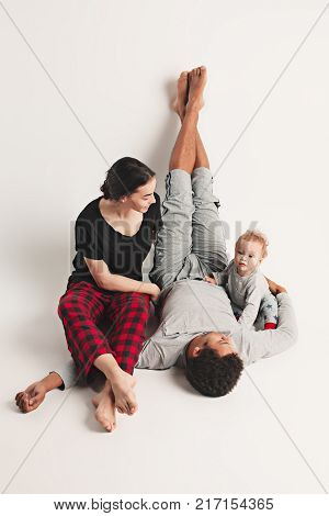 A happy family of afro man and caucasian woman and child on white studio background