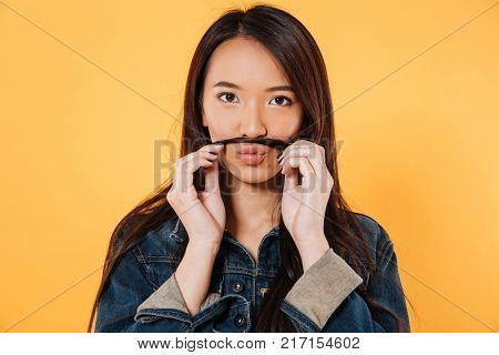 Playful asian woman in denim jacket making fake mustache with her hair and looking at the camera over yellow background