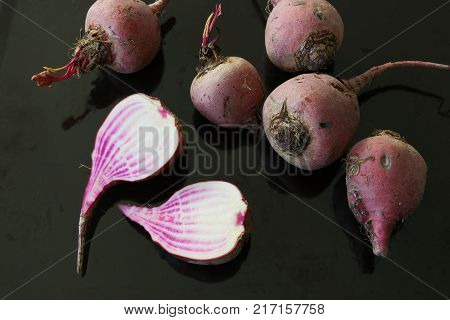 Raw chioggia beets or candy cane beets on dark background.