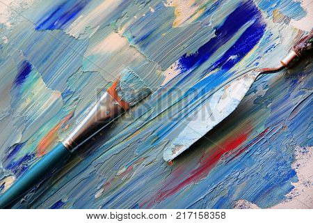 Closeup background of palette with brush and palette knife