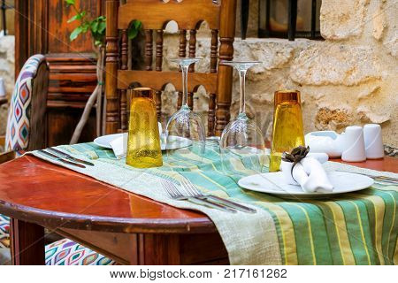 Served table with Cutlery in restaurant on narrow touristic street in the tourist routes. Walk around the old resort town Rethymno in Greece. Culture and Mediterranean cuisine on island Crete