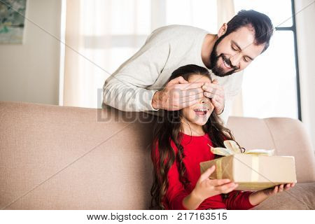 smiling father presenting gift box to daughter