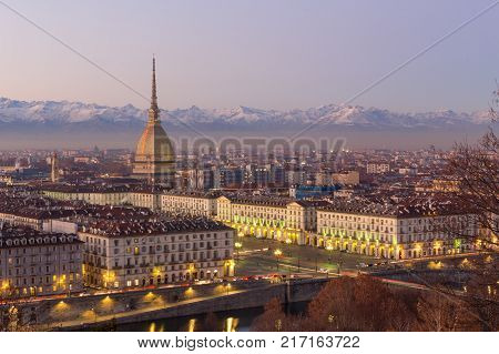 Turin Italy: cityscape at sunrise with details of the Mole Antonelliana of Torino towering over the city. Scenic colorful light on the snowcapped Alps in the background.