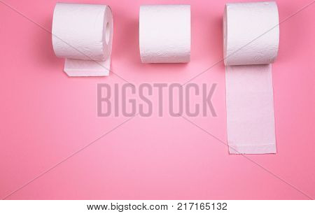 A few rolls of toilet paper on a bright colored background