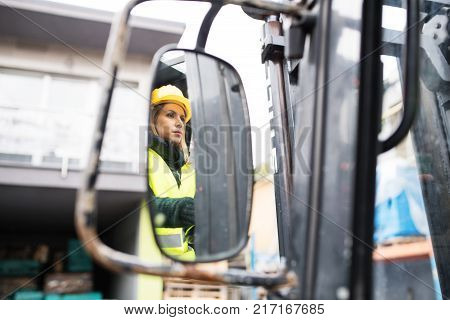 Female forklift truck driver in an industrial area. A woman sitting in the fork lift outside a warehouse. Reflection in a rear view mirror.