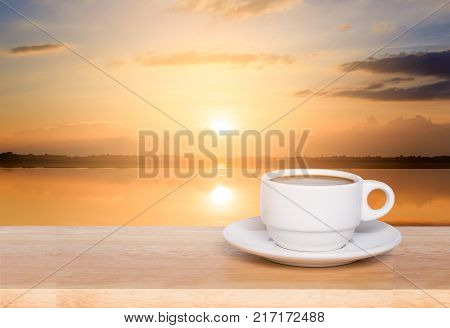 white coffee cup on wood table and view of sunset in the river background