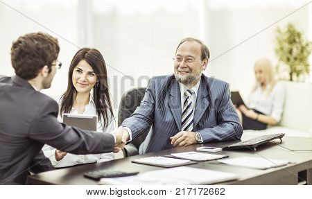 handshake business partners after discussion of the financial terms of the contract.the photo has a empty space for your text