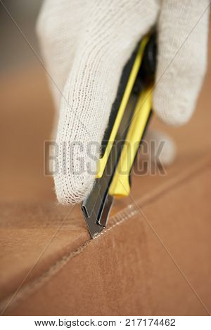 Opening box with paper knife close-up. Hand in glove with knife unpacking