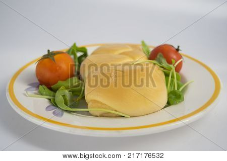 scamorza cheese on a wooden dish with cherry tomatoes and lettuce