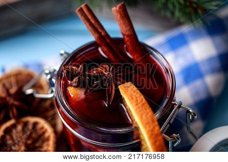 Mulled wine in a glass. Christmas hot mulled wine in a glass with spices and citrus fruit. Mulled wine with cinnamon, anise and orange. Christmas atmosphere