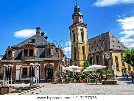 FRANKFURT, GERMANY-JULY 21, 2017: The historic Café Hauptwache (popular meeting place since its opening over 100 years ago) and St. Katharine church in the middle of the city